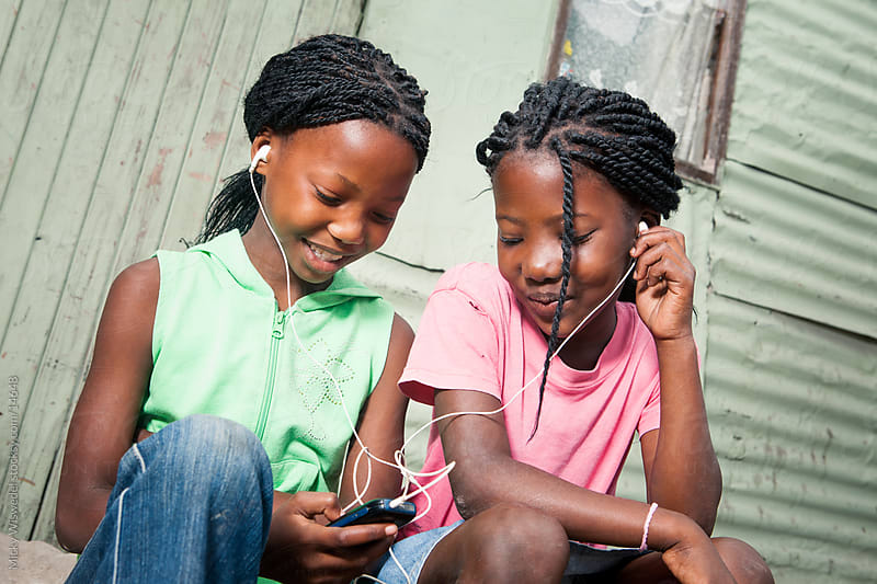 African girls listening to music by Micky Wiswedel for Stocksy United