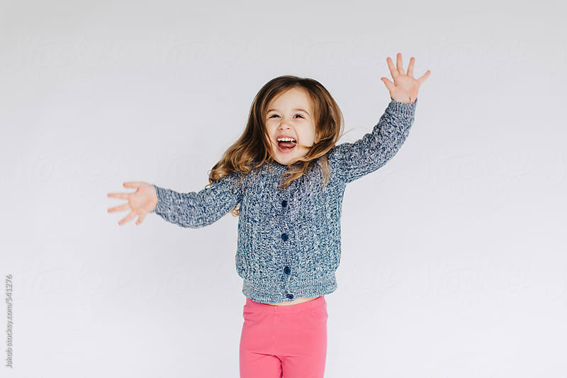 Cute and sassy young girl dancing in front a white wall by Jakob for Stocksy United