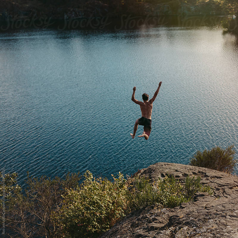 Young, brave man jumping off cliff in summer by Rob and Julia Campbell for Stocksy United