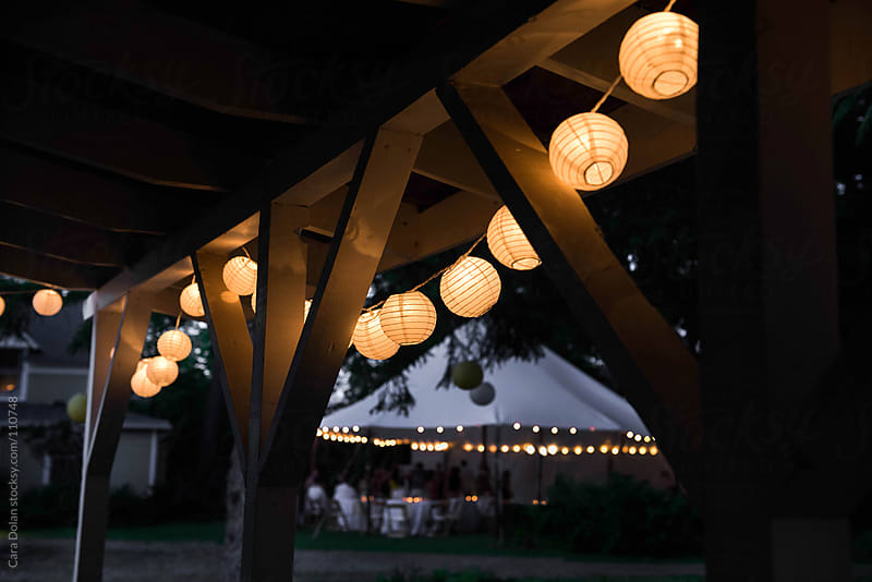 Party lanterns on barn with party tent in background by Cara Dolan for Stocksy United