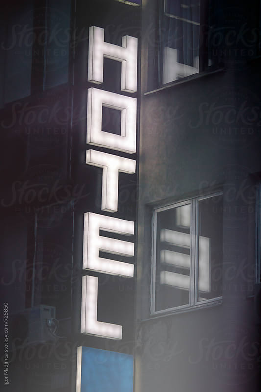 hotel entrance ,illuminated advertising sign, the atmosphere of the street by Igor Madjinca for Stocksy United
