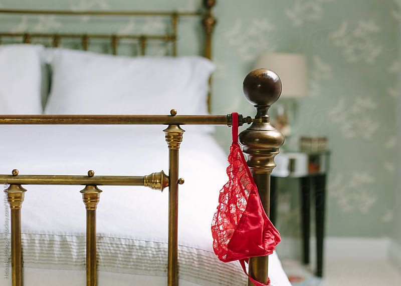 Red knickers draped over the end of a bed. by Helen Rushbrook for Stocksy United