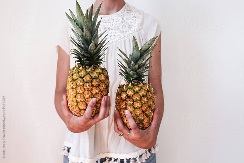 Young woman holding pineapple by Treasures & Travels for Stocksy United