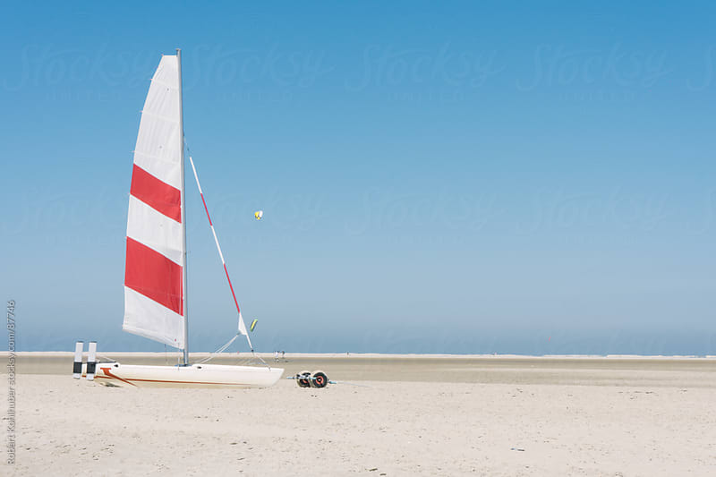 Sailboat on a beach at the north sea by Robert Kohlhuber for Stocksy United