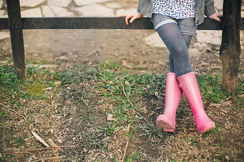Girl in Boots Sitting on a Fence by Lumina for Stocksy United