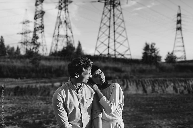 Young couple walking  ander the power lines by Evgenij Yulkin for Stocksy United