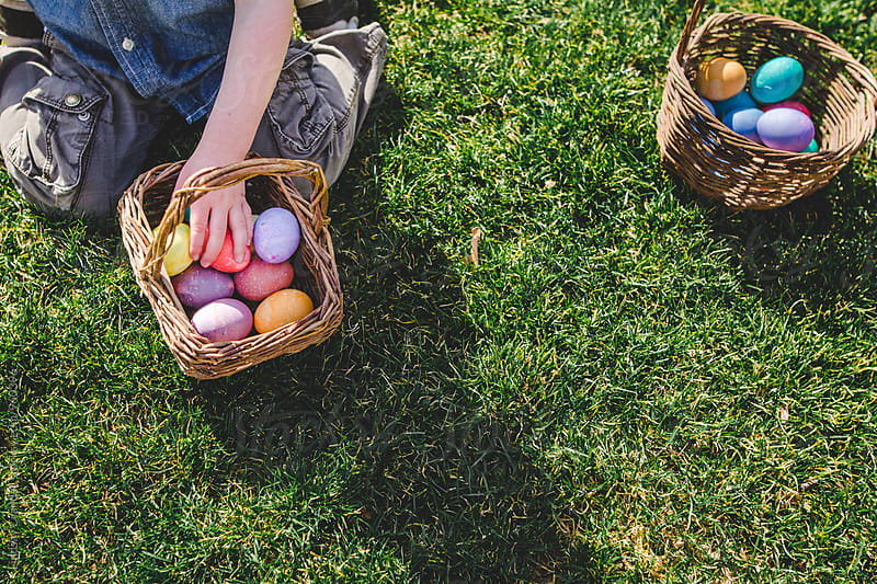 Child kneeling in grass with Easter eggs by Lindsay Crandall for Stocksy United