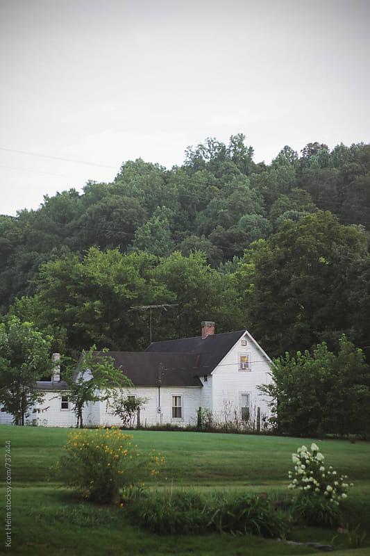 White Farm House on Edge of Forest by Kurt Heim for Stocksy United