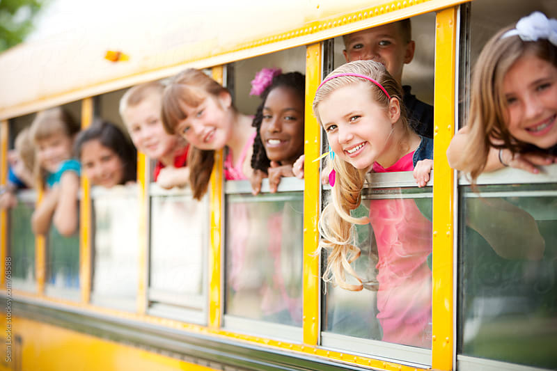 School Bus: Cute Kids Looking Out Window by Sean Locke for Stocksy United