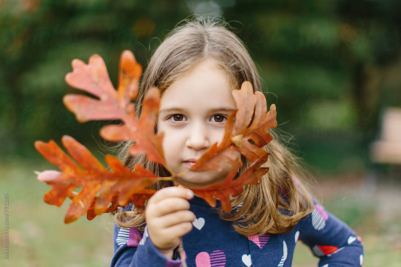 Cute young girl holding up a branch with leaves to her face by Jakob for Stocksy United