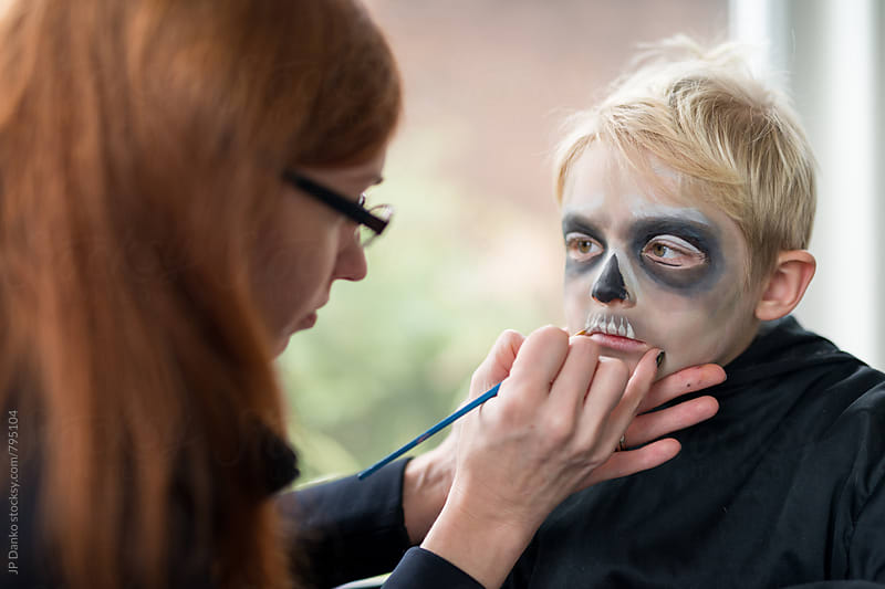 Mother Applying Little Boys Halloween Costume Make Up by JP Danko for Stocksy United