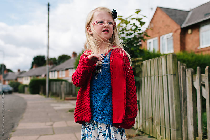 Girl with long blonde hair, glasses and pretty clothes on a suburban street in England.  by Julia Forsman for Stocksy United