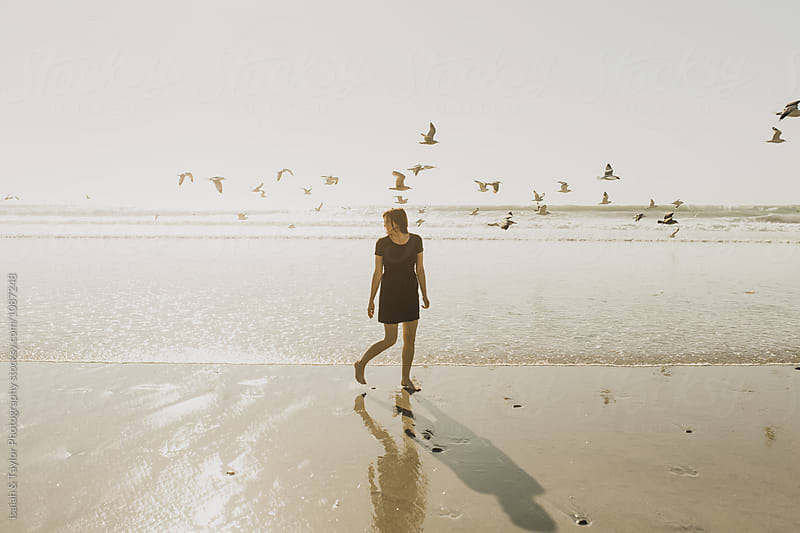 Young woman walking on beach by Isaiah & Taylor Photography for Stocksy United