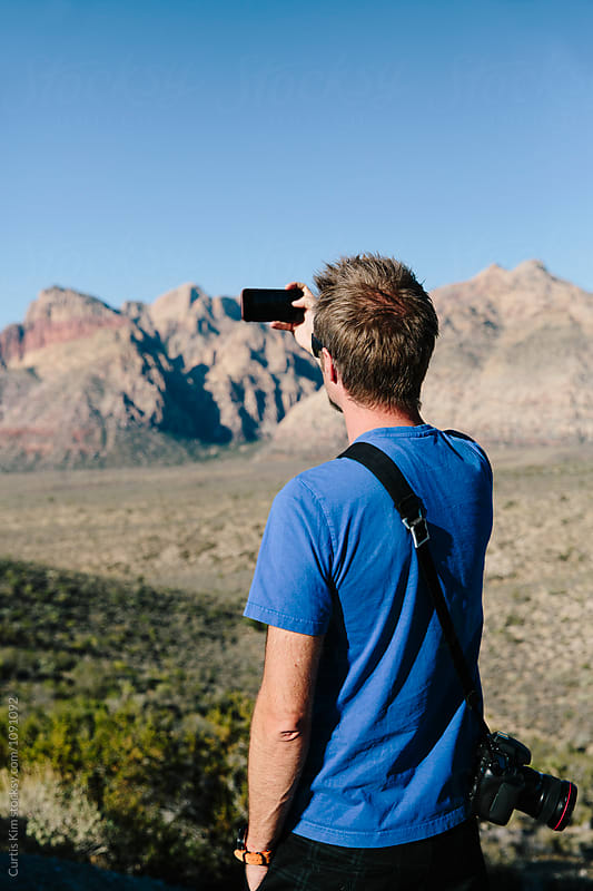 Man with camera taking picture of mountains in the desert by Curtis Kim for Stocksy United