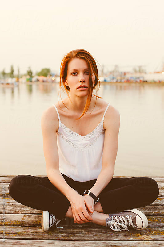 Young woman sitting on the dock by Aleksandra Kovac for Stocksy United
