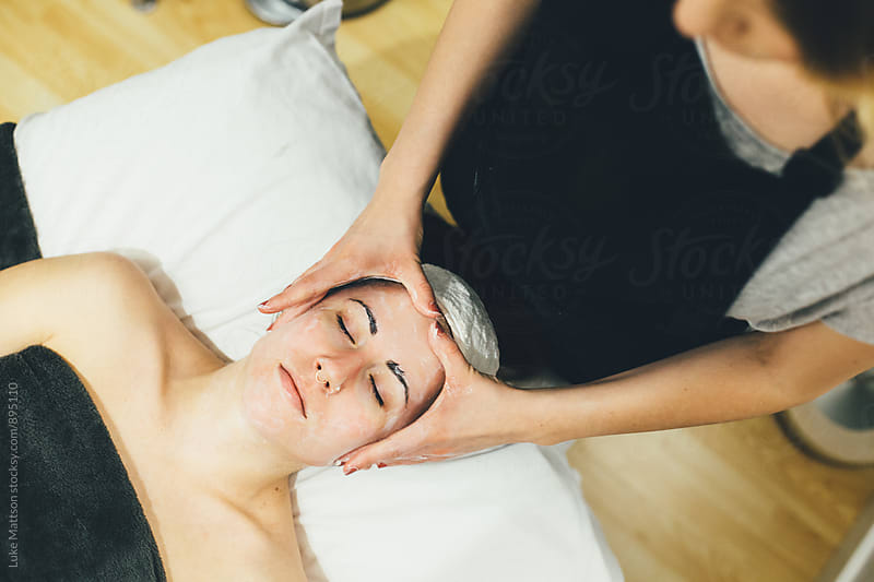 Esthetician Massaging Head And Face Of Young Woman During Facial by Luke Mattson for Stocksy United
