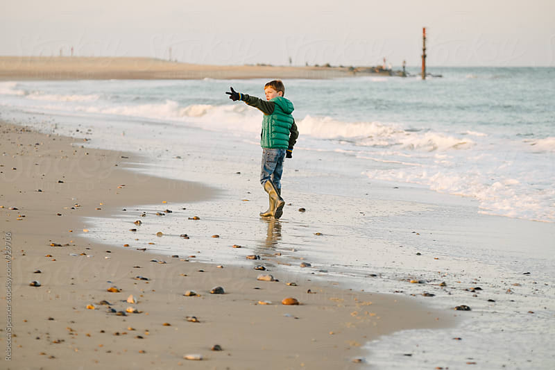 Child wearing winter clothes gestures on the beach by Rebecca Spencer for Stocksy United
