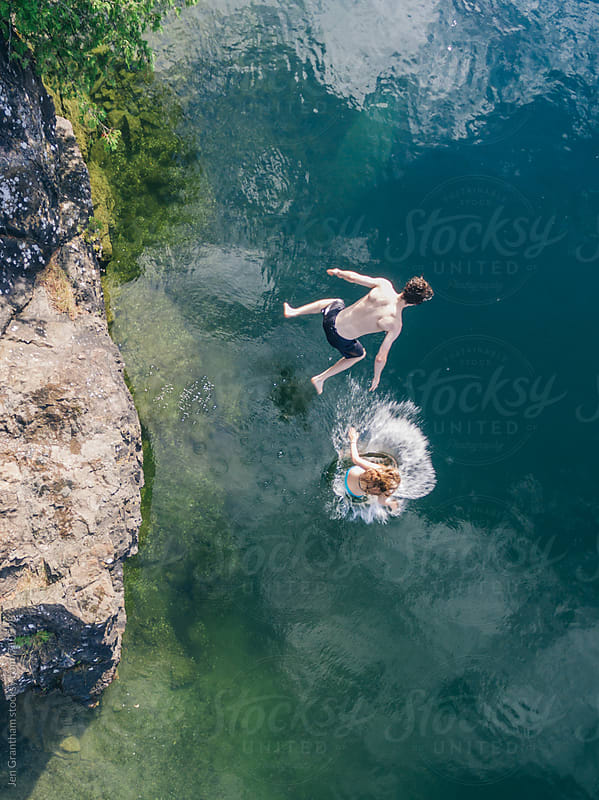 Overhead drone image of teenagers jumping off a rock  by Jen Grantham for Stocksy United