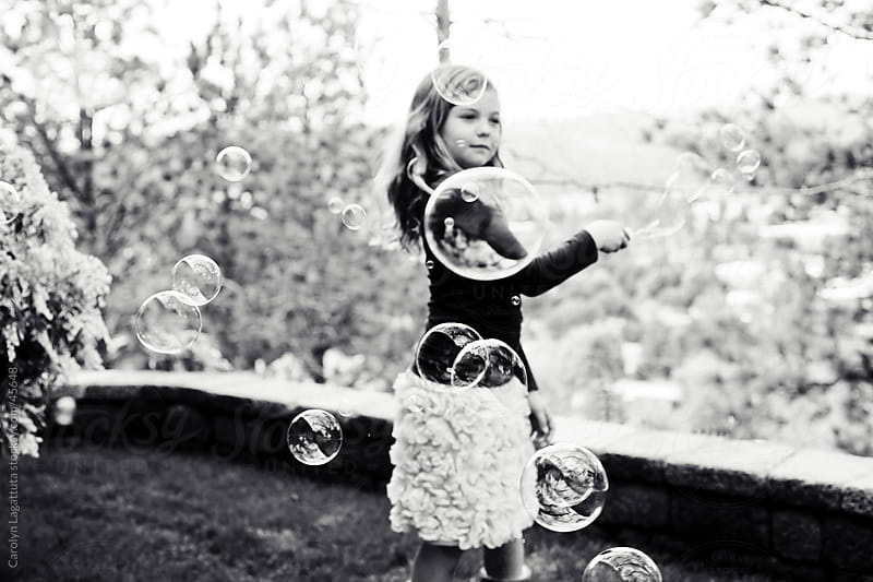 Black and white photo of a little girl playing with bubbles by Carolyn Lagattuta for Stocksy United
