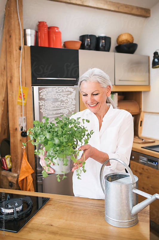 Senior woman with cilantro plant and watering can by Lilly Bloom for Stocksy United