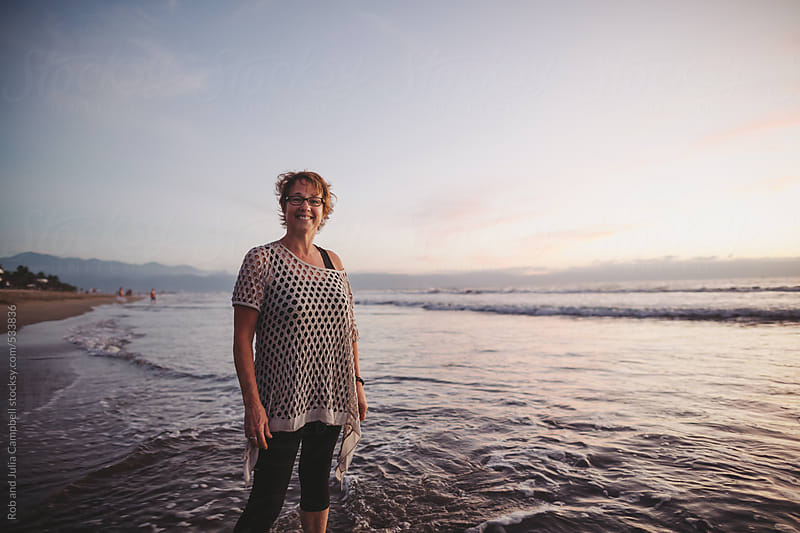 Content middle aged, retired woman smiling outside on ocean beach at sunset by Rob and Julia Campbell for Stocksy United