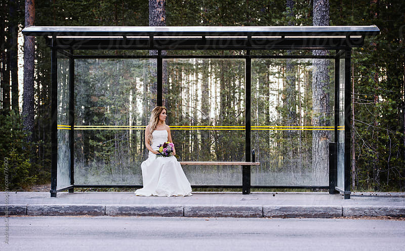 a lonely bride waiting on a bus stop by Andreas Gradin for Stocksy United