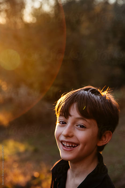 Boy with rim light around his head looking at camera by Beatrix Boros for Stocksy United