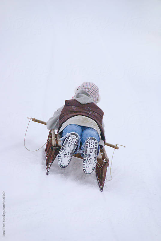 A young girl sleds down a slope on an old wooden sled by Tana Teel for Stocksy United