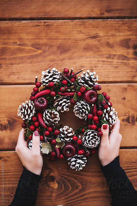 Woman's hands holding holiday decorations by Luca Pierro for Stocksy United