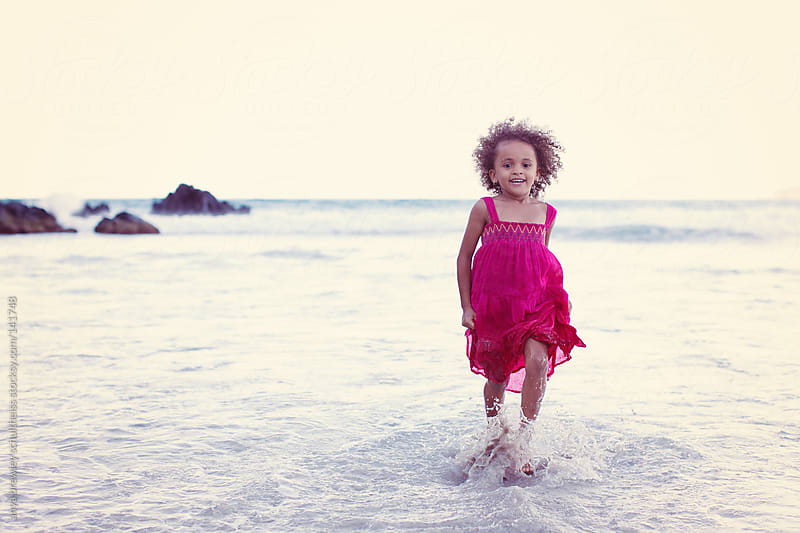 Young girl in pink playing on the beach by anya brewley schultheiss for Stocksy United