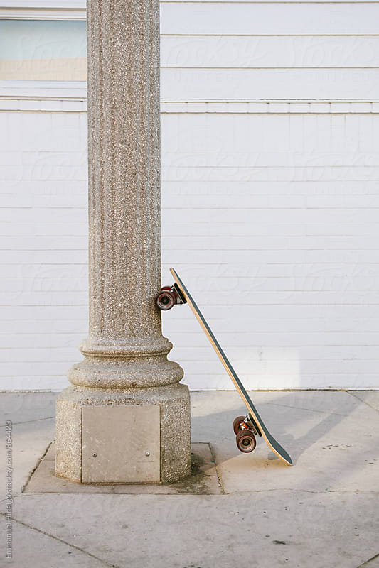 Abandoned skateboard against a light post by Emmanuel Hidalgo for Stocksy United