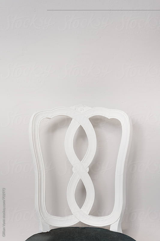 white vintage chair against a plain wall, by Gillian Vann for Stocksy United