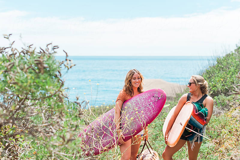 Two Young Women Surfers Carrying Surfboards Away from the Ocean by Briana Morrison for Stocksy United