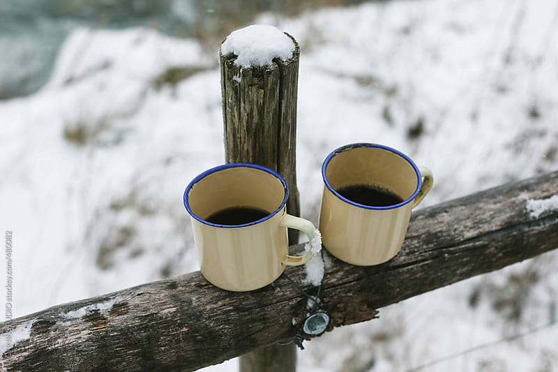 Two hot cups of coffee on a snowy landscape.  by BONNINSTUDIO for Stocksy United