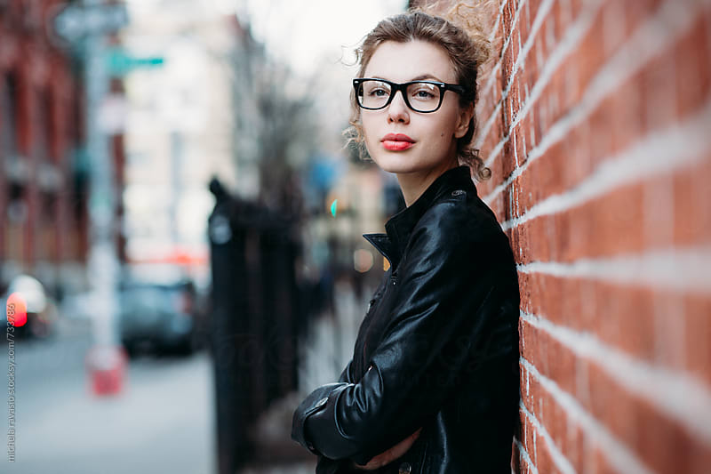 Portrait of attractive woman leaning on the brick wall by michela ravasio for Stocksy United