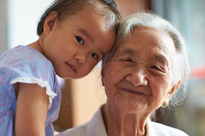 portrait of senior asian woman with her great granddaughter by Bo Bo for Stocksy United