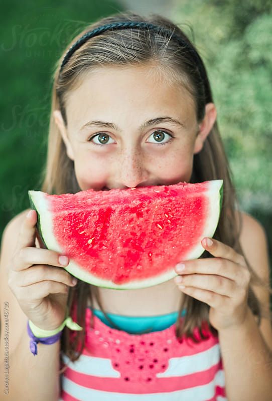 Little girl holding a piece of watermelon in front of her mouth with big eyes by Carolyn Lagattuta for Stocksy United