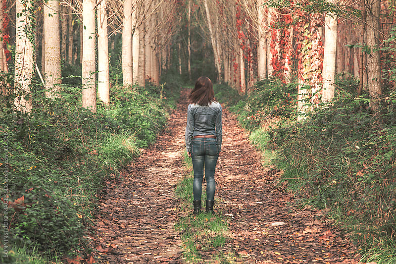 Young woman back on a forest road. Autumn landscape. by BONNINSTUDIO for Stocksy United