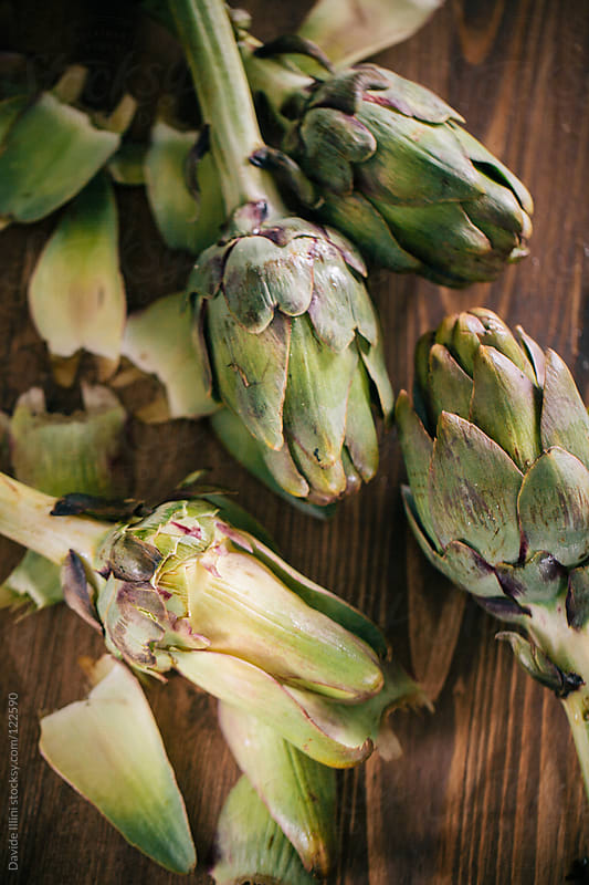 Raw artichokes on a table by Davide Illini for Stocksy United