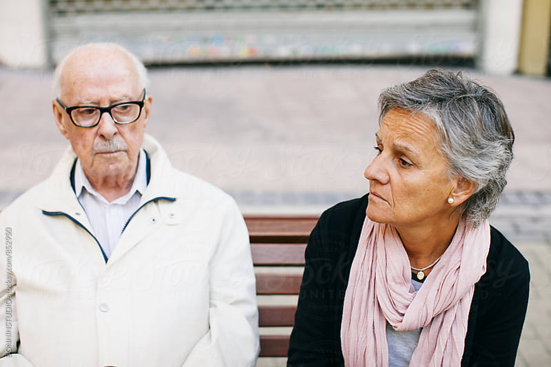 Elderly father and his daughter sitting on bench. by BONNINSTUDIO for Stocksy United