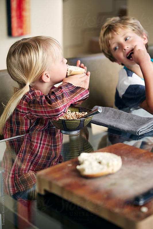 Kids eating breakfast at the dining room table by Trinette Reed for Stocksy United