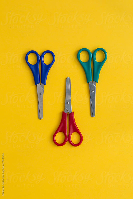 Red, Blue, Green scissors on yellow background by Melanie Kintz for Stocksy United
