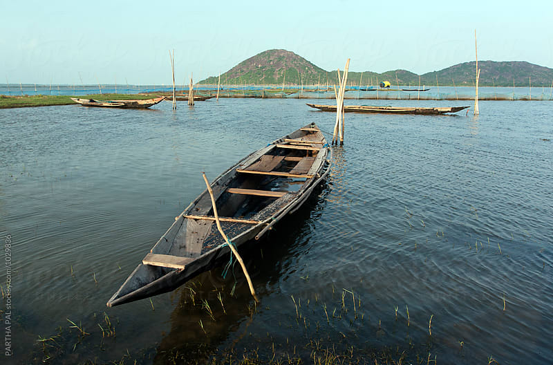 Fishing boat resting in a big lake,India by PARTHA PAL for Stocksy United