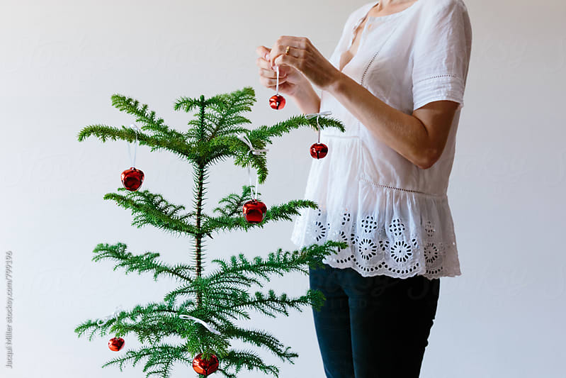 Unrecognisable woman decorating a small Norfolk Island Pine Tree for Christmas - horizontal by Jacqui Miller for Stocksy United