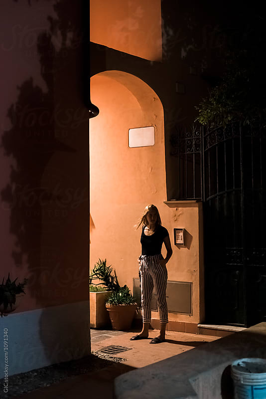 Young woman standing in a old Italian street at night by GIC for Stocksy United