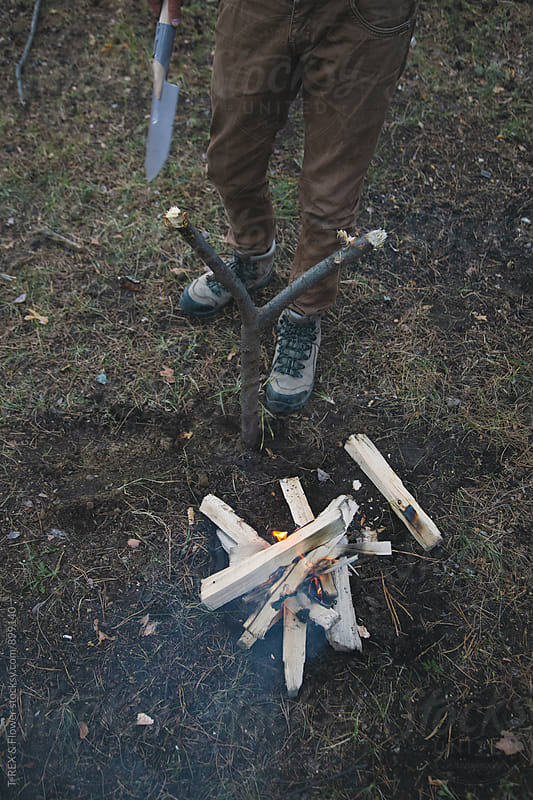 Mn with shovel near campfire by Danil Nevsky for Stocksy United