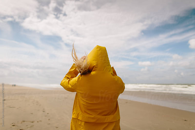 Woman on a windy beach wearing a yellow raincoat by Denni Van Huis for Stocksy United