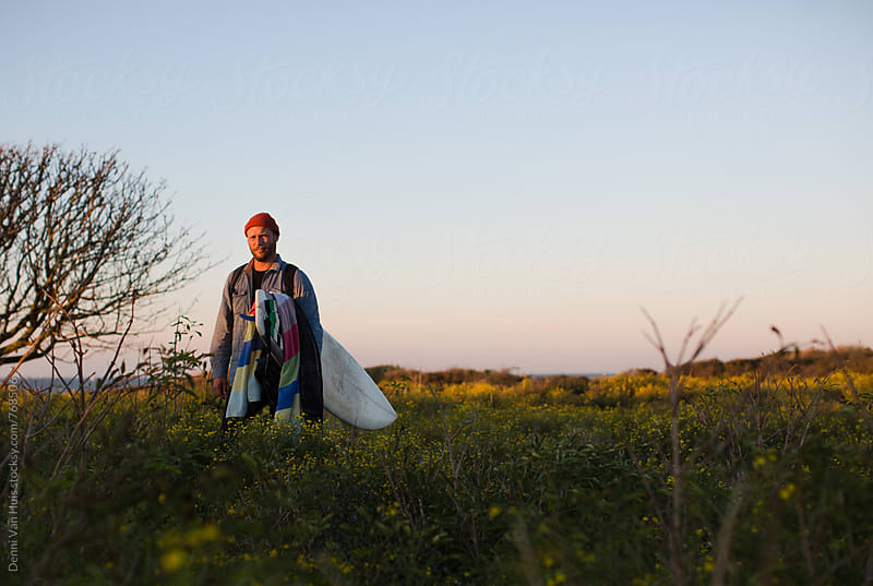 Man standing in the dunes with surfboards next to a tree in the evening sun by Denni Van Huis for Stocksy United