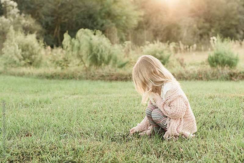 A young Girl Crouching On The Ground by Alison Winterroth for Stocksy United