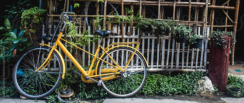 Yellow bicycle parked against white fence in Chiang Mai, Thailan by Soren Egeberg for Stocksy United